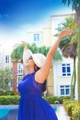 Beautiful woman in blue dress and white hat with arms wide apart happy by the pool