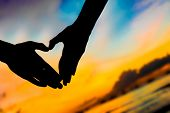 picture of love-making  - silhouettes of young loving couple on bright sunset sky and sea background making heart shape with their hands - JPG