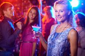 Stylish woman with martini glass posing at nightclub