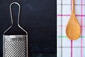wooden spoon, metal grater and tablecloth over blackboard background