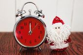 picture of father time  - Santa Claus or Father Frost and vintage alarm clock with red dial on wooden background. Showing time twelve midnight