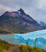 Colossal Perito Moreno glacier in Lake Argentino, surrounded by mountains. Los Glaciares National Park. Sunny summer day