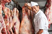 Portrait of happy male butcher standing by meat hanging in slaughterhouse