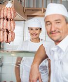 Portrait of beautiful happy female butcher with male colleague in butchery