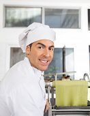 Side view portrait of smiling male chef by pasta machine at commercial kitchen