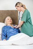 Female caregiver examining senior woman with stethoscope in bedroom at nursing home