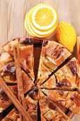 baked food: apple pie cuts on wooden plate served with fresh lemon, mandarin, and cinnamon sticks on table