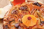 baked food: round apple pie on wooden plate served with fresh lemon, mandarin, and cinnamon sticks on table