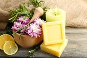 Handmade soap with the branches of rosemary, fresh flowers and lemon slices on wooden background
