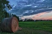 Hay bales on a meadow against beautiful sky with clouds in sunset in hdr photo