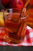 Apple cider in glass and bottle with cinnamon sticks and fresh apples on wooden background