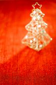 abstract red flaring background with tin focus line in front and glitter christmas tree decoration defocused bokeh