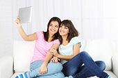 Beautiful girls twins with electronic tablet on sofa