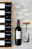 High angle shot of a case of red wine bottles next to a single bottle two wineglasses and cork screws on a rustic white wood table. Vertical format.