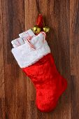 Christmas stocking filled with presents hanging from a hook on a wood wall. Vertical format.