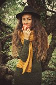 winter autumn girl in wood eat an apple stand by tree wearing hat, wool scarf and green dress