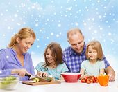 food, family, children, happiness and people concept - happy family with two kids making dinner over blue sky and snowflakes background