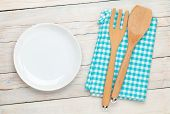 Empty plate and kitchen utensil over white wooden table background. View from above