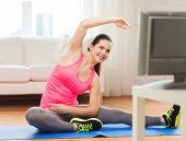 fitness, workout, healthy living and diet concept - smiling teenage girl stretching on floor and watching tv at home