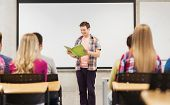 education, high school, teamwork and people concept - smiling student boy with notebook standing and reading in front of students in classroom