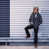 foto of overcoats  - Fashionable young man wearing fur hat and warm overcoat corrugated iron wall on background  - JPG