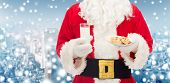 christmas, holidays, food, drink and people concept - close up of santa claus with glass of milk and cookies over snowy city background