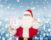 christmas, holidays and people concept - man in costume of santa claus with clock showing twelve pointing finger up over snowy city background