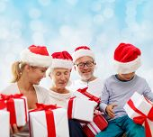 family, christmas, generation, holidays and people concept - happy family in santa helper hats with gift boxes sitting over blue lights background