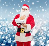 christmas, holidays and people concept - man in costume of santa claus with notepad over snowy city background