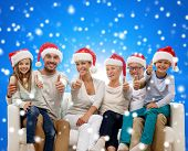 family, happiness, generation, holidays and people concept - happy family in santa helper hats sitting on couch and showing thumbs up gesture over blue snowy background