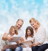 family, holidays, technology and people - smiling mother, father and little girls with tablet pc computers over blue lights background