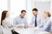 business, architecture and office concept - happy team of architects and designers with color samples in office