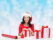 christmas, holidays, celebration, decoration and people concept - smiling woman in santa helper hats with decorating paper and gift boxes over blue lights background