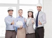 business, architecture and office concept - happy team of architects in office showing thumbs up