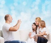 family, holidays, technology and people - smiling mother, father and little girls with camera over blue lights background