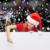 christmas, holidays and advertisement concept - happy girl in santa helper hat pointing finger on blank white board over snowy night city background