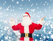 christmas, holidays and people concept - man in costume of santa claus with raised hands over snowy city background