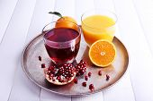 Glasses of fresh orange and pomegranate juice on tray on white wooden table