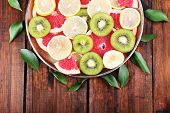 Ripe slices lemon, kiwi and grapefruit on tray on wooden background