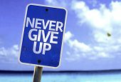Never Give Up sign with a beach on background