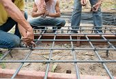 Workers Are  Preparing Steel Poles For Building House