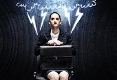 Upset businesswoman sitting on chair with suitcase in hands