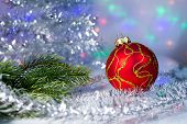 Red Christmas ball and tree branch on the background lights garl