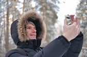 Man in winter clothes making selfie using smartphone