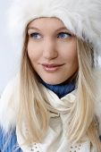 Winter portrait of attractive young blonde woman smiling, looking away.