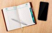 Modern mobile phone and Year business project planner book with pen on wood table