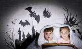 Two little kids reading book under blanket