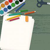 Art supplies on wooden desk (aquarel colors, pencils, papers & scissors)