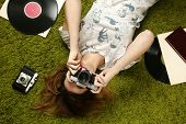 image of lp  - Young woman taking picture with an old vintage camera