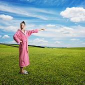 dissatisfied housewife screaming and pointing at something over green meadow and blue sky